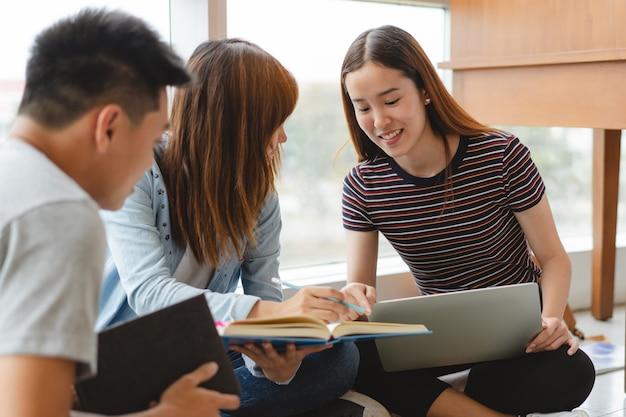 Groep aziatische studenten die gegevens voor thuiswerkopdracht onderzoeken in bibliotheek.