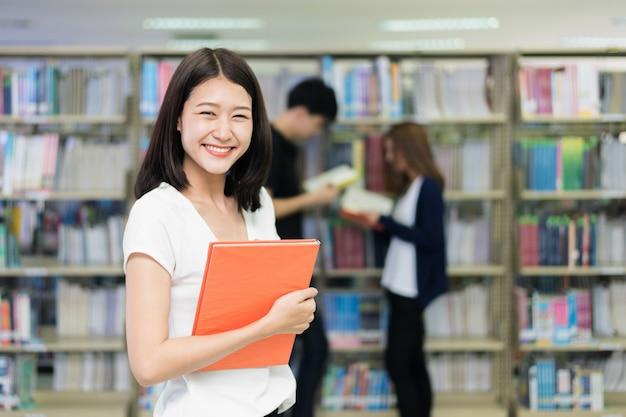 Groep aziatische studenten die samen in bibliotheek bij universiteit bestuderen.