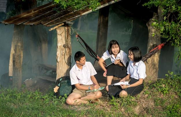 Groep aziatische studenten in eenvormig samen studeren bij openlucht.