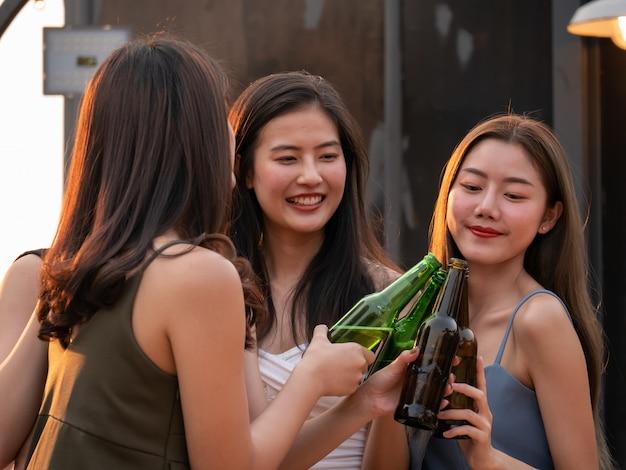 Groep aziatische vriend die en bij terraspartij toejuichen drinken. jongeren die glas met bier roosteren bij restaurant op het dak