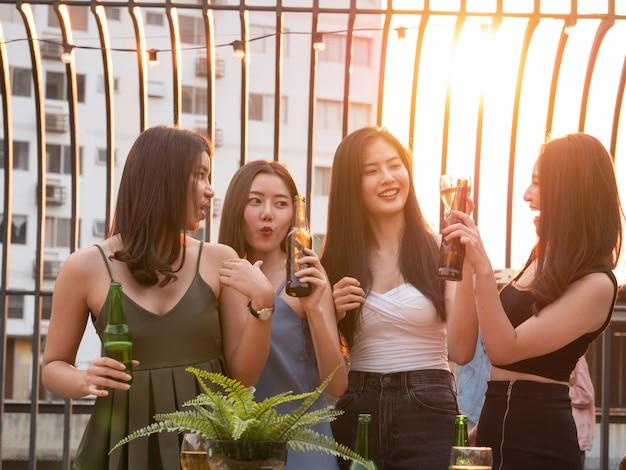 Groep aziatische vriend die en bij terraspartij toejuichen drinken. jongeren genieten en opknoping op het dak bij zonsondergang
