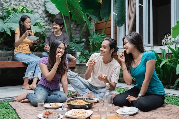 Groep aziatische vrienden die plezier hebben tijdens het eten en drinken in de achtertuin