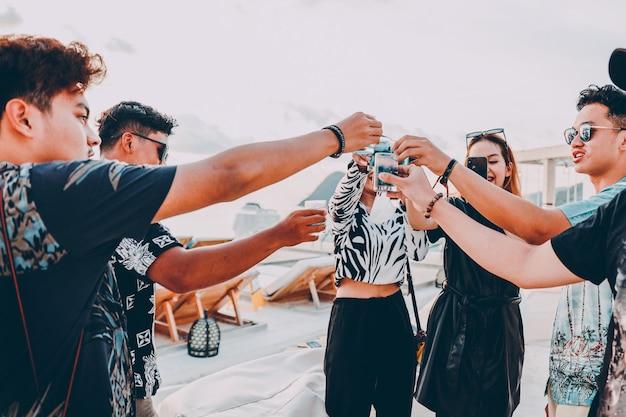 Groep aziatische vrienden juichen met blauwe tropische cocktails op zomervakantie