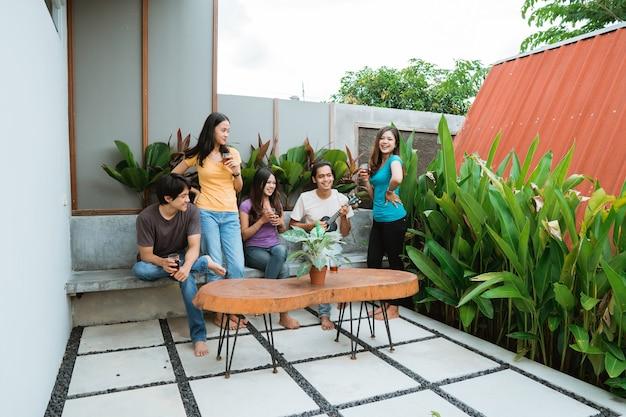 Groep aziatische vrienden plezier zingen en gitaar spelen samen in de achtertuin