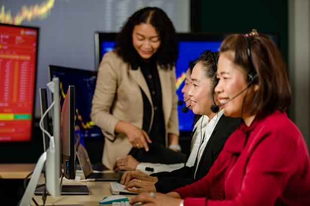 Groep aziatische vrouwelijke klantenservicemedewerkers draagt microfoonheadsets zitten glimlachend vooraan dagelijkse grafiekgrafiek computermonitorscherm praten en handelen kopen, verkopen aandelenmarkt online met de klant.