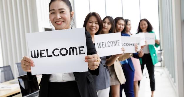 Groep aziatische vrouwelijke zakenmensen voegt zich bij elkaar om welkomswoorden te begroeten en vast te houden voor een teken van geluk en plezier voor het komen van iets of iemand.