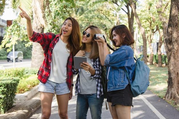 Groep aziatische vrouwen die camera met behulp van om foto te maken terwijl het reizen bij park in stedelijke stad in bangkok
