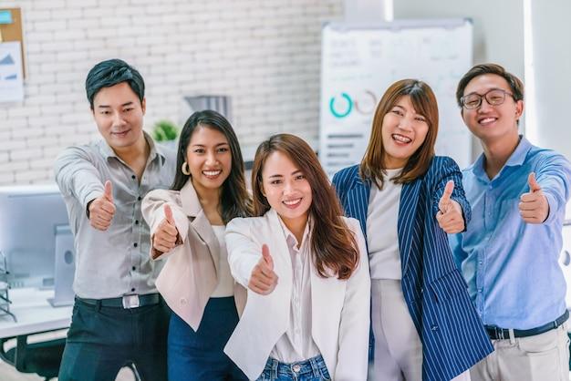 Groep aziatische zakenmensen die duimen opdagen en samen naar de camera kijken