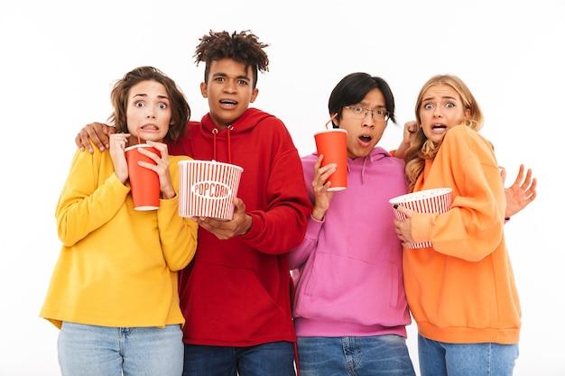 Groep bang multiraciale vrienden kijken naar een film, popcorn eten, frisdrank drinken geïsoleerd