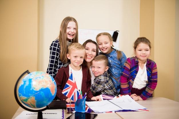 Groep basisschoolkinderen en leraar werken aan bureaus in de klas.