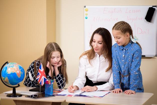 Groep basisschoolkinderen en leraar werken aan bureaus in klas.