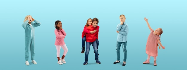 Groep basisschoolkinderen of leerlingen die dromen in kleurrijke vrijetijdskleding op blauw