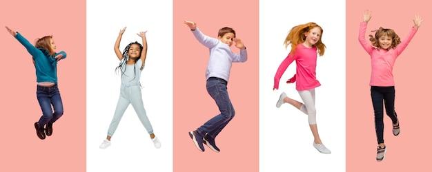 Groep basisschoolkinderen of leerlingen die in kleurrijke vrijetijdskleding springen op bicolored
