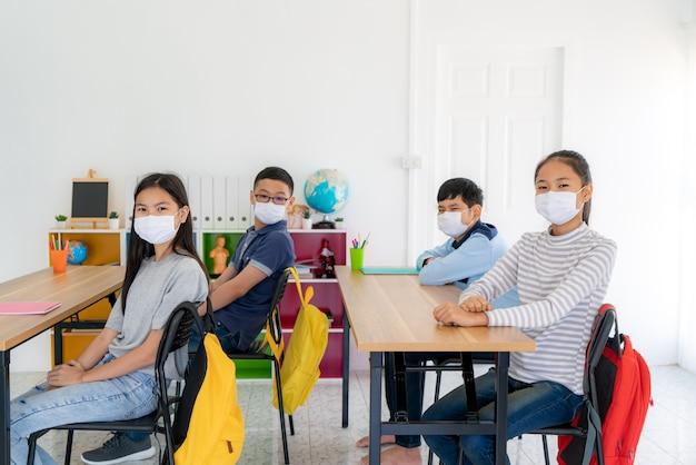 Groep basisschoolstudenten die een hygiënisch masker in de klas dragen en glimlachen om gelukkig te zijn terwijl ze terug naar school gaan, heropenen hun school, nieuw normaal voor onderwijsconcept.