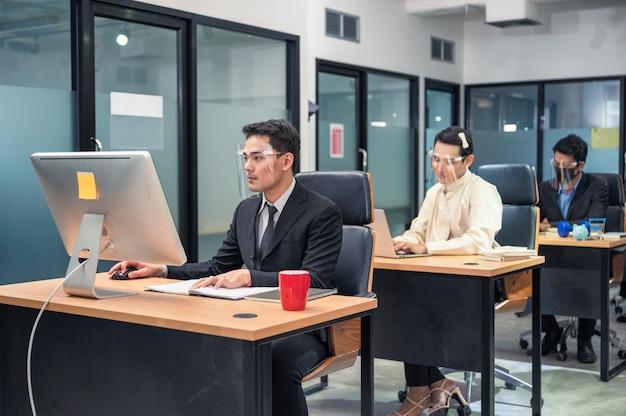 Groep beambte die met computer bij bureau in modern bureau werkt