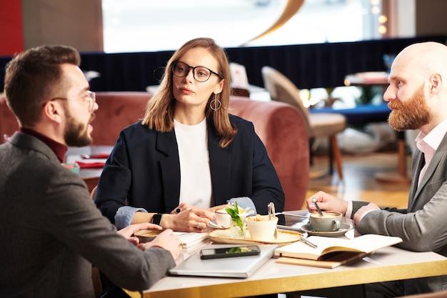 Groep bedrijfsleiders die aan tafel in restaurant zitten en ideeën en plannen uitwisselen