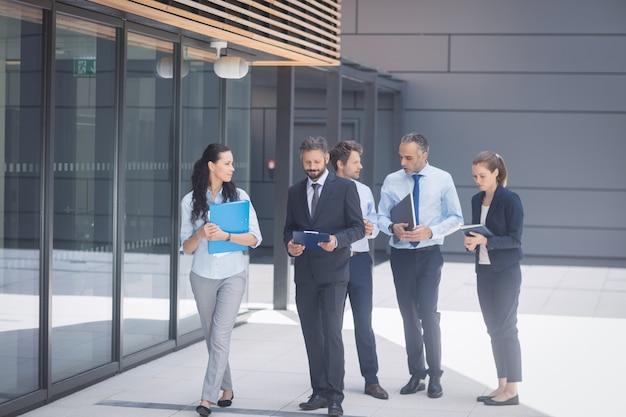 Groep bedrijfsmensen die buiten de bureaubouw lopen