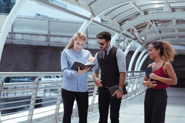 Groep bedrijfsmensen die datum van klantenbenoeming controleren op notitieboekje terwijl het lopen in de stad