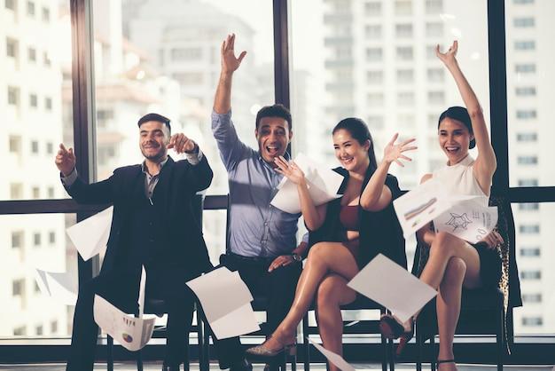 Groep bedrijfsmensen die door hun handelspapieren in de lucht te werpen vieren