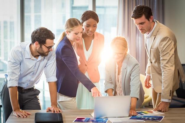 Groep bedrijfsmensen die gebruikend laptop op elkaar inwerken