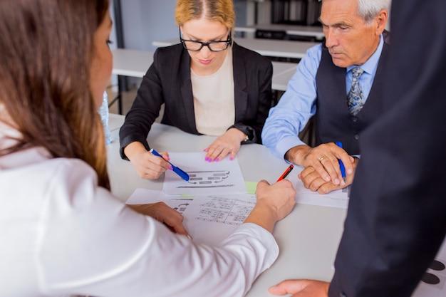 Groep bedrijfsmensen die het businessplan bespreken bij de lijst in het bureau