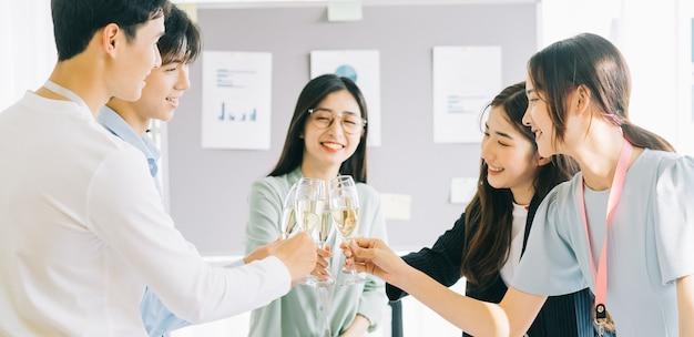 Groep bedrijfsmensen die het succes van het project vieren bij het bedrijf, eindejaarsfeest, gelukkig nieuwjaar