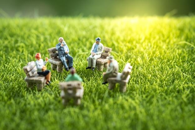 Groep bedrijfsmensen die in een tuin zitten.