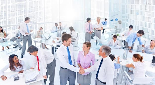 Groep bedrijfsmensen die in het bureau samenkomen
