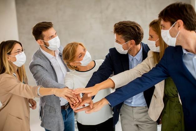 Groep bedrijfsmensen die met beschermende gezichtsmaskers handen samen in het bureau houden