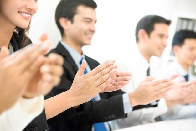 Groep bedrijfsmensen die op de vergadering toejuichen