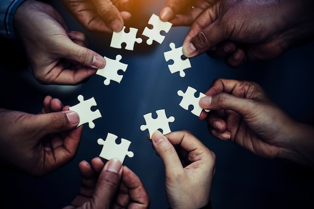 Groep bedrijfsmensen die puzzel assembleren en teamsteun vertegenwoordigen