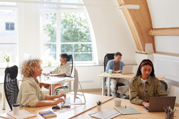 Groep bedrijfsmensen in vrijetijdskleding die op hun werkplekken zitten en computers gebruiken in hun werk op kantoor