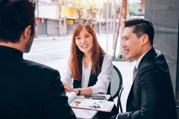 Groep bedrijfsmensengroepswerkvergadering in bedrijfsdistrict die over nieuwe kans spreken in economisch groeien