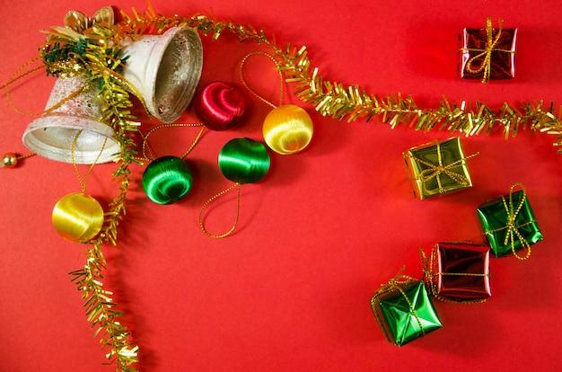 Groep bel, bal en cadeau in kerstmis op rode achtergrond op bovenaanzicht