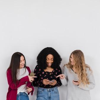 Groep beste vrienden die op een telefoon kijken