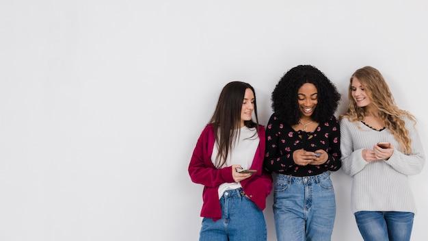Groep beste vrienden die op een telefoon met exemplaarruimte kijken