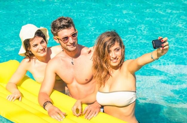 Groep beste vrienden die selfie bij zwembad op geel luchtbed nemen