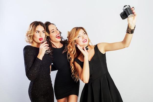 Groep beste vrienden, drie elegante meisjes in zwarte luxe jurk zelfportret maken, rode wijn drinken, poseren.