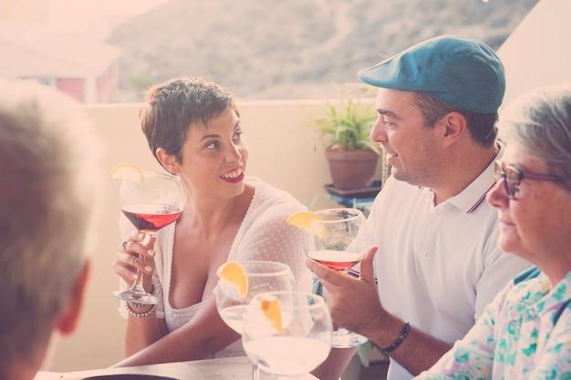 Groep blanke mensen die buiten wijncocktail drinken met vrienden van verschillende leeftijden
