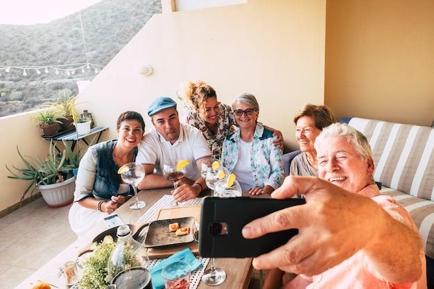 Groep blanke mensen vieren samen thuis op het terras