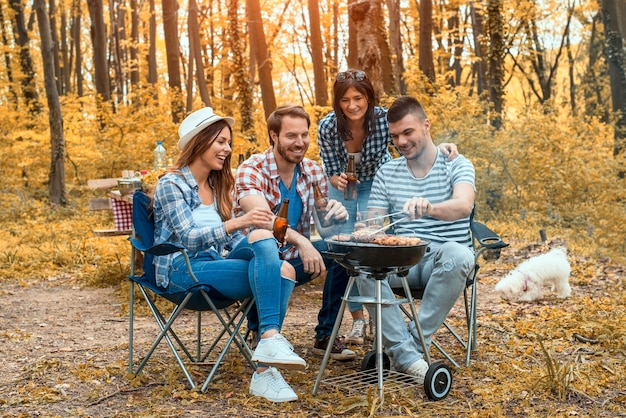 Groep blanke vrienden die barbecueën en plezier hebben in het bos