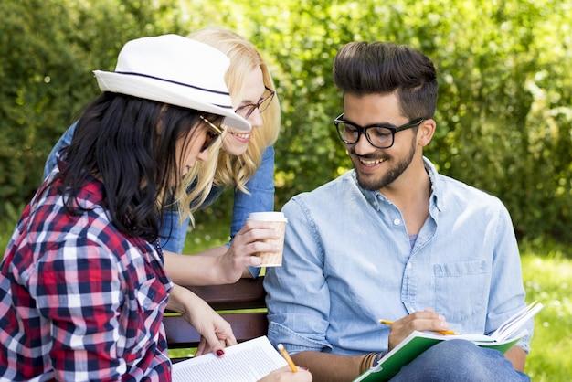 Groep blanke vrienden studeren op een bankje bij daglicht