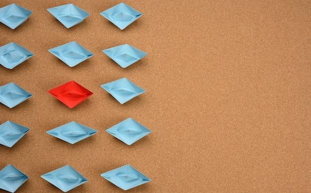 Groep blauwe papieren boten en een rode in het midden op een bruin oppervlak. het concept van een unieke en buitengewone persoonlijkheid in een team. getalenteerde medewerker, wees jezelf