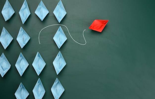 Groep blauwe papieren boten vaart in de ene richting, een rode vaart in de tegenovergestelde richting. het concept van een buitengewone persoonlijkheid, handelen in strijd met de fundamenten van de samenleving