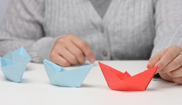 Groep blauwe papieren boten volgt een rode boot voor een witte achtergrond. het concept van een sterke en charismatische leider in een team, die de massa manipuleert