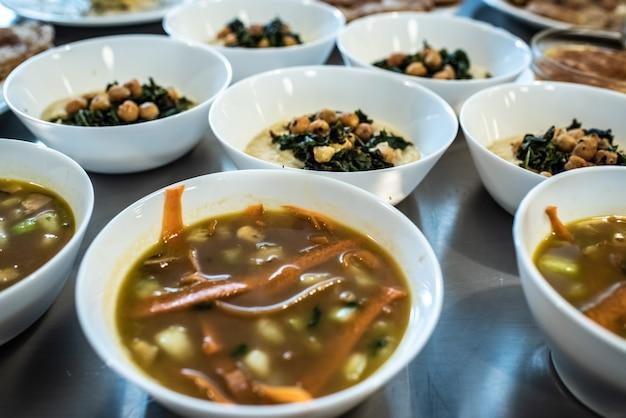 Groep borden met verschillende soorten soepen in hete kommen.