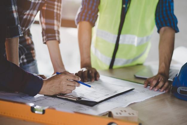 Groep bouwersploeg die en de tekening van het bouwhuis plannen bespreken.