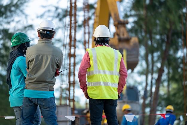 Groep bouwingenieur en veiligheidsambtenaar bij bouwwerf