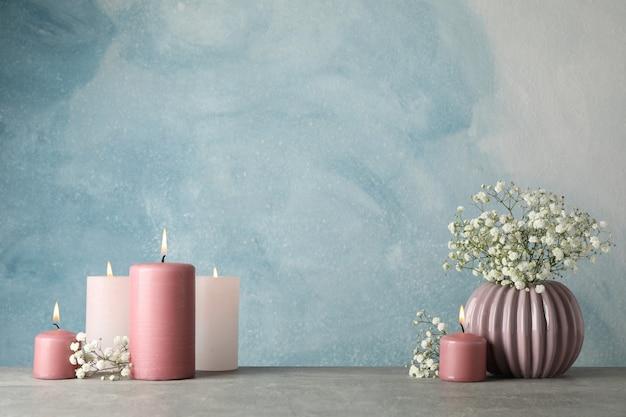 Groep brandende kaarsen en bloem op blauw