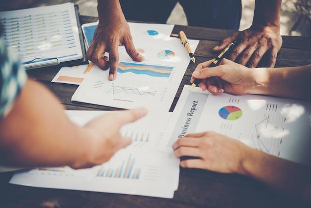 Groep business people analyse met marketing rapport grafiek, jonge specialisten bespreken zakelijke ideeën voor een nieuw digitaal opstartproject.